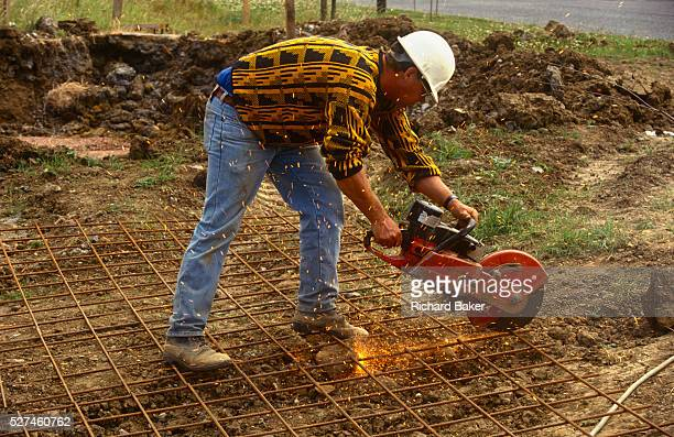 A building worker grinds steel caging on a construction project site in Milton Keynes UK Bending down to ground level the workman touches his grinder...