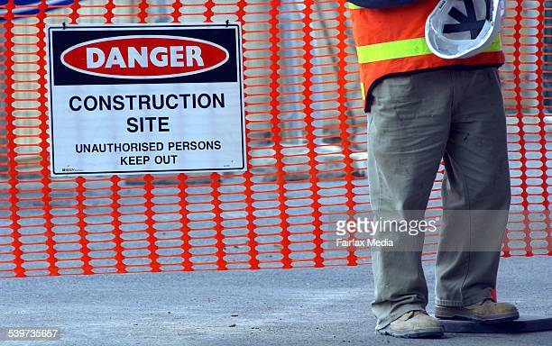 A building worker holding his hard hat on a construction site beside a warning sign reading 'Danger Construction Site' 2 September 2003 AFR Picture...