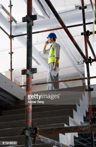 Building worker using cell phone on building site : Stock Photo