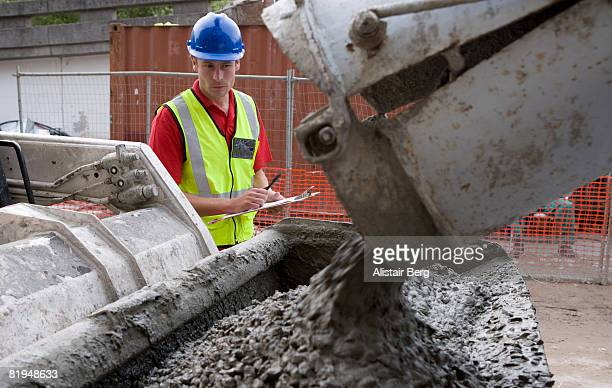 Building worker watching concrete being poured  from lorry