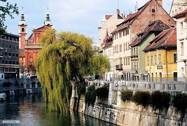 Buildings along the banks of the Ljubljanica River with the Franciscan Church of the Annunciation in the background Ljubljana Slovenia