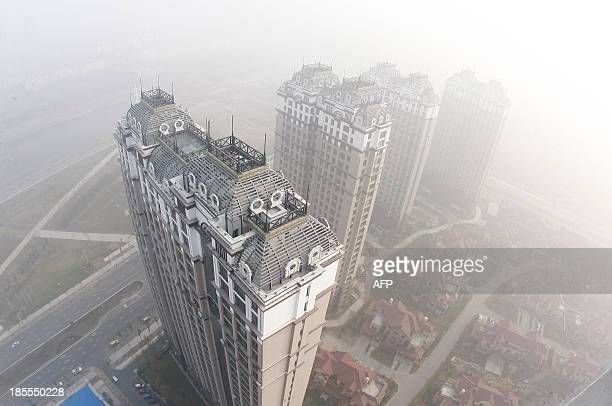 Buildings and streets are seen under heavy smog in Harbin northeast China's Heilongjiang province on October 22 2013 Thick smog enveloped a major...
