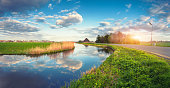 Buildings and trees near the water canal at sunrise in Netherlands. Colorful blue sky with clouds. Summer landscape. Rural scene. Cloudy sky reflected in water. Nature background. Vintage style