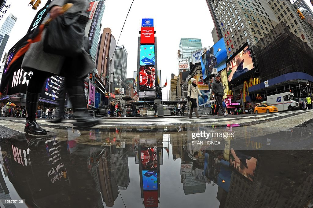 Buildings are reflected in a puddle December 27, 2012 in New York's Times Square. AFP PHOTO/Stan HONDA