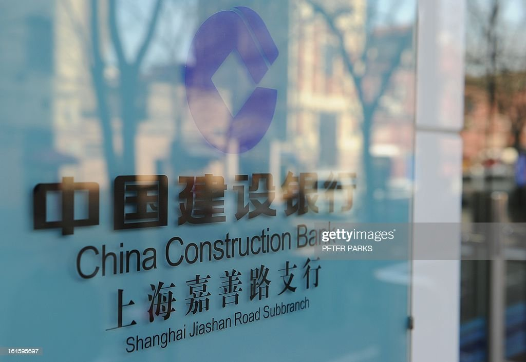 Buildings are reflected in a window of a branch of the China Construction Bank in Shanghai on March 25, 2013. China Construction Bank, one of the country's top four lenders, said its net profit rose 14.1 percent year-on-year in 2012, lifted by growth in net interest income. AFP PHOTO / Peter PARKS