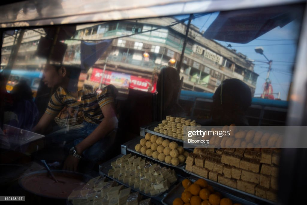 Buildings are reflected in the window of a roadside stall selling sweets in Kolkata, India, on Tuesday, Feb. 19, 2013. India's slowest economic expansion in a decade is limiting profit growth at the biggest companies even as foreigners remain net buyers of the nation's stocks, according to Kotak Institutional Equities. Photographer: Brent Lewin/Bloomberg via Getty Images