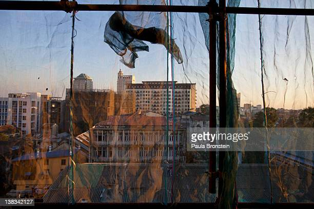Buildings are seen in Yangon through a netting used to protect buildings from construction sites February 6 2012 in Yangon Myanmar In the unreliable...