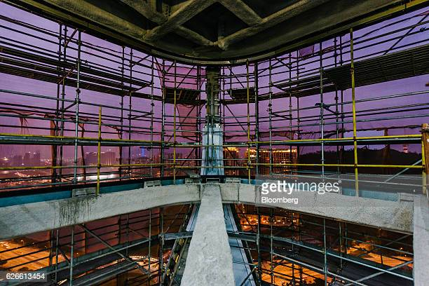 Buildings are seen through scaffolding surrounding Morpheus Melco Crown Entertainment Ltd's new hotel tower under construction at the company's City...