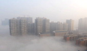 Buildings are shrouded in smog on January 14 2014 in Changsha Hunan Province of China China's Meteorological Administration issued a yellow warning...