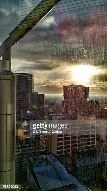Buildings In City Against Sky Seen Through Glass Window