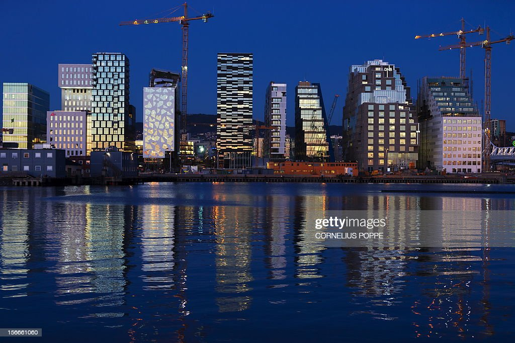 Buildings of The Barcode Project are reflected on the water at sunset in Oslo on November 18 2012 The row of new highrise buildings are part of a...