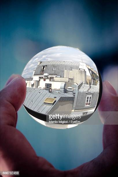 Buildings Refracted In Sphere Crystal Ball Held By Persons Hand