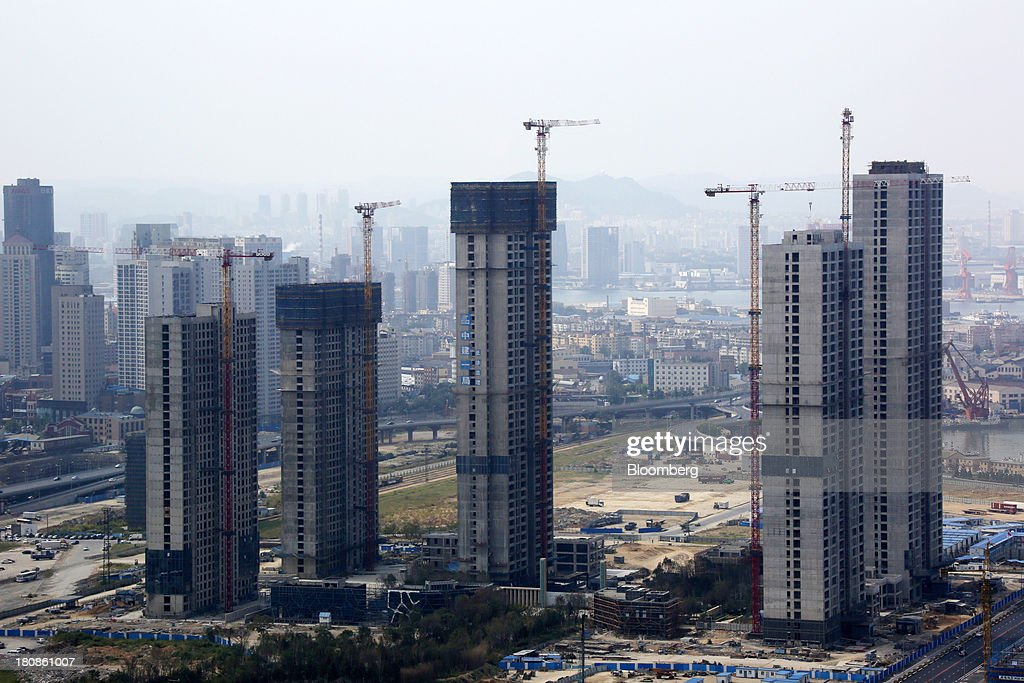 Buildings sit under construction near the Dalian Wanda Center in Dalian, China, on Friday, Sept. 13, 2013. Goldman Sachs Group Inc. this month raised its estimate for China's economic growth for the third and fourth quarters, citing improving global demand and a stronger-than-expected domestic industrial recovery. Photographer: Tomohiro Ohsumi/Bloomberg via Getty Images