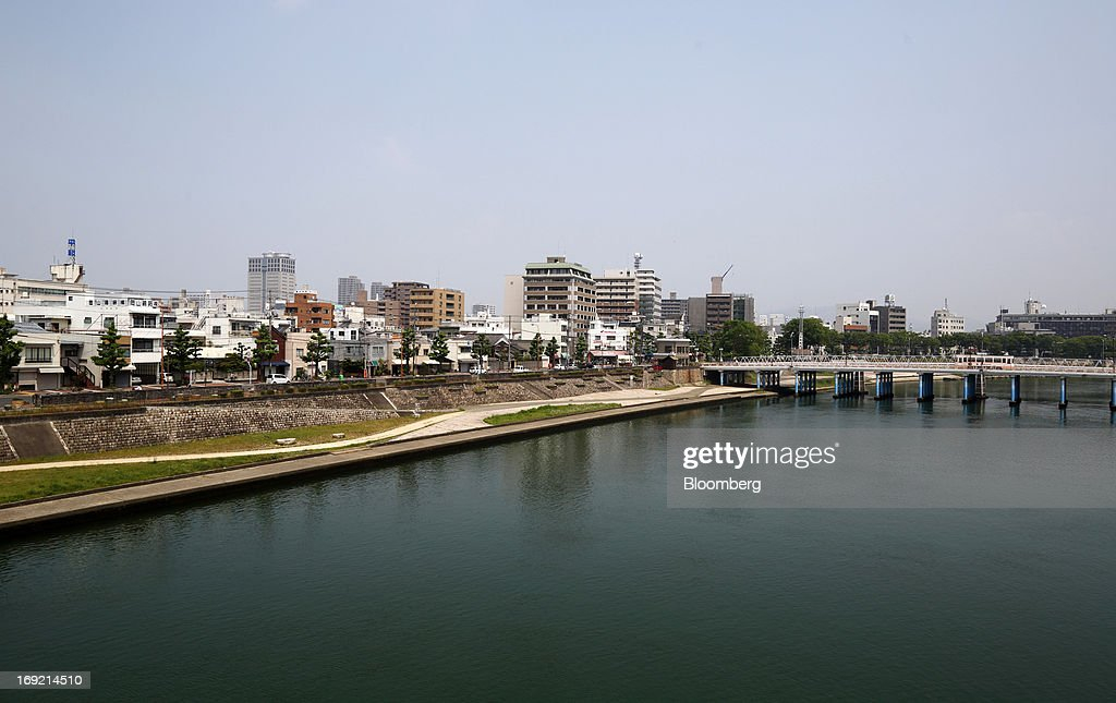 Buildings stand along the Asahi river in Okayama, Japan, on Tuesday, May 21, 2013. The Bank of Japan, forecast to maintain plans for expanded monetary easing at a meeting ending on May 22, is targeting 2 percent inflation in two years after more than 10 years of entrenched deflation. Photographer: Tomohiro Ohsumi/Bloomberg via Getty Images