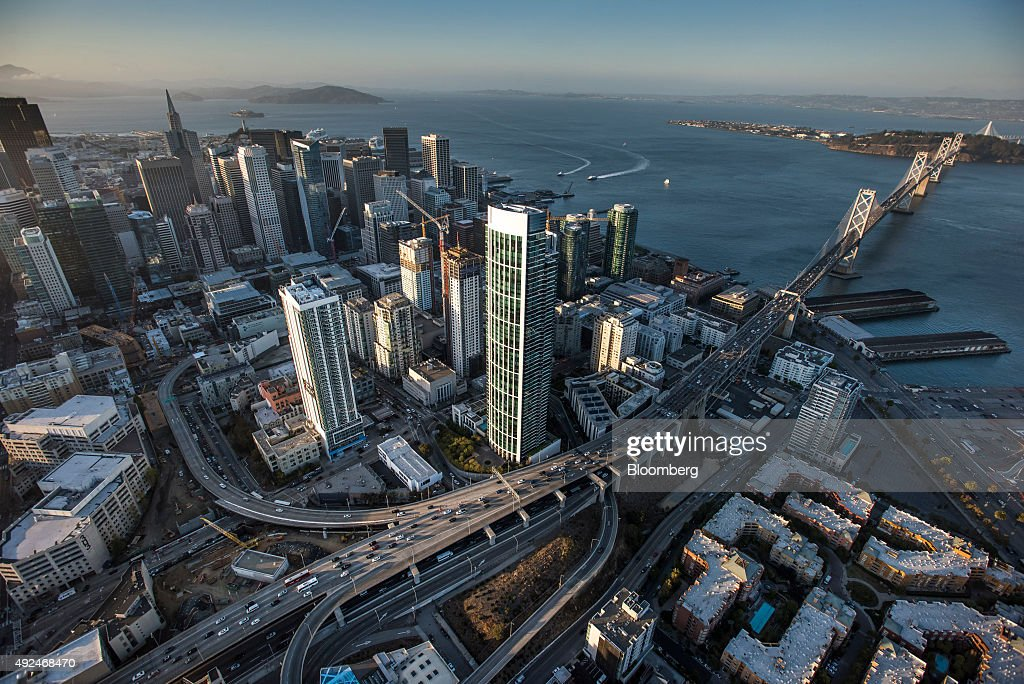 Buildings stand in the skyline of downtown as cars travel over the San Francisco-Oakland Bay Bridge from Treasure Island in this aerial photograph taken above San Francisco, California, U.S., on Monday, Oct. 5, 2015. With tech workers flooding San Francisco, one-bedroom apartment rents have climbed to $3,500 a month, more than in any other U.S. city. Photographer: David Paul Morris/Bloomberg via Getty Images