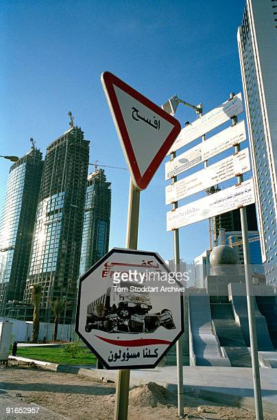 Buildings under construction along the corniche in Doha Qatar May 2008 In the foreground is a road safety sign depicting a crash with the caption...