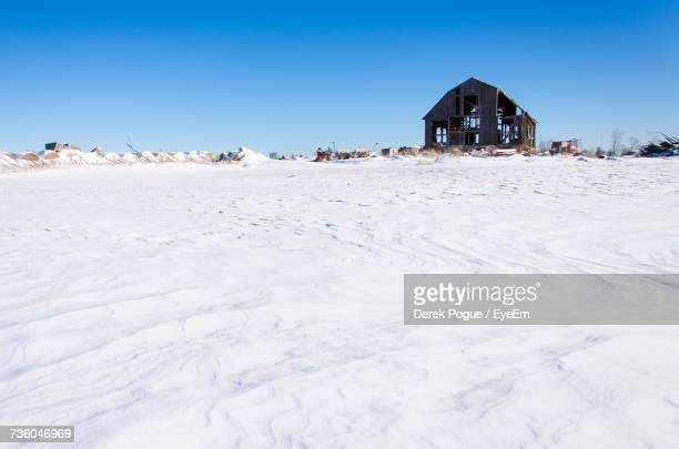 Built Structure On Snow Covered Landscape Against Clear Blue Sky