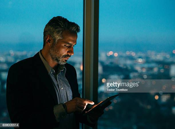 Buisnessman Using Tablet At Night