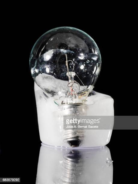 Bulb led inside a chunk of ice, concept of the rise of the price of the electrical energy for the home