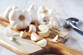 Bulbs of garlic on cutting board and garlic press on light background