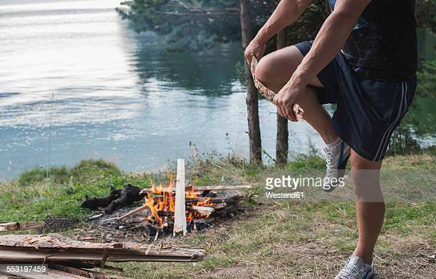 Bulgaria, Man breaking wood for camp fire at lakeshore