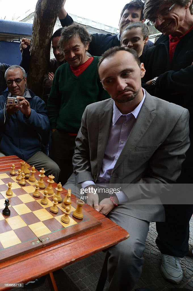 Bulgarian chess grandmaster Veselin Topalov gestures as he plays against Uruguayan Carlos Ferrari (out of frame) near to a newsstand in Montevideo on March 18, 2013. Topolov, World Chess Championship 2006, is in Uruguay to support a national program of the Minister of Education and Culture to promote chess between lower classes. Ferrari is the owner of the kiosk, next to which Montevideo citizens play chess on the sidewalk all year. AFP PHOTO / Daniel CASELLI