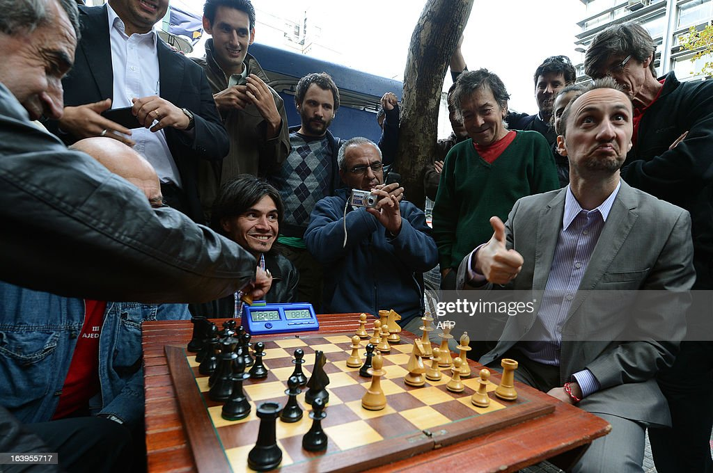 Bulgarian chess grandmaster Veselin Topalov (R) gestures as he plays against Uruguayan Carlos Ferrari near to a newsstand in Montevideo on March 18, 2013. Topolov, World Chess Championship 2006, is in Uruguay to support a national program of the Minister of Education and Culture to promote chess between lower classes. Ferrari is the owner of the kiosk, next to which Montevideo citizens play chess on the sidewalk all year. AFP PHOTO / Daniel CASELLI