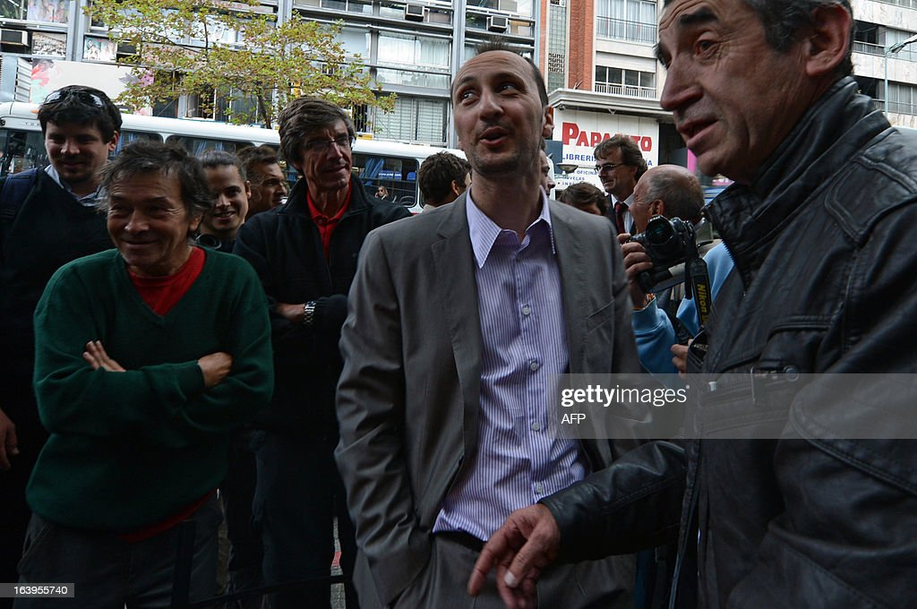Bulgarian chess grandmaster Veselin Topalov (2-R) gestures at the end of a match against Uruguayan Carlos Ferrari (R) near to a newsstand in Montevideo on March 18, 2013. Topolov, World Chess Championship 2006, is in Uruguay to support a national program of the Minister of Education and Culture to promote chess between lower classes. Ferrari is the owner of the kiosk, next to which Montevideo citizens play chess on the sidewalk all year. AFP PHOTO / Daniel CASELLI