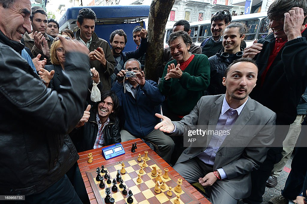 Bulgarian chess grandmaster Veselin Topalov (R) gestures next to Uruguayan Carlos Ferrari (L) at the end of a match near to a newsstand in Montevideo on March 18, 2013. Topolov, World Chess Championship 2006, is in Uruguay to support a national program of the Minister of Education and Culture to promote chess between lower classes. Ferrari is the owner of the kiosk, next to which Montevideo citizens play chess on the sidewalk all year. AFP PHOTO / Daniel CASELLI