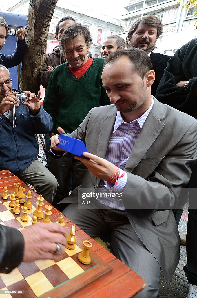Bulgarian chess grandmaster Veselin Topalov looks at a chess timer before playing a chess match against Uruguayan Carlos Ferrari (out of frame), near to a newsstand in Montevideo on March 18, 2013. Topolov, World Chess Championship 2006, is in Uruguay to support a national program of the Minister of Education and Culture to promote chess between lower classes. Ferrari is the owner of the kiosk, next to which Montevideo citizens play chess on the sidewalk all year. AFP PHOTO / Daniel CASELLI