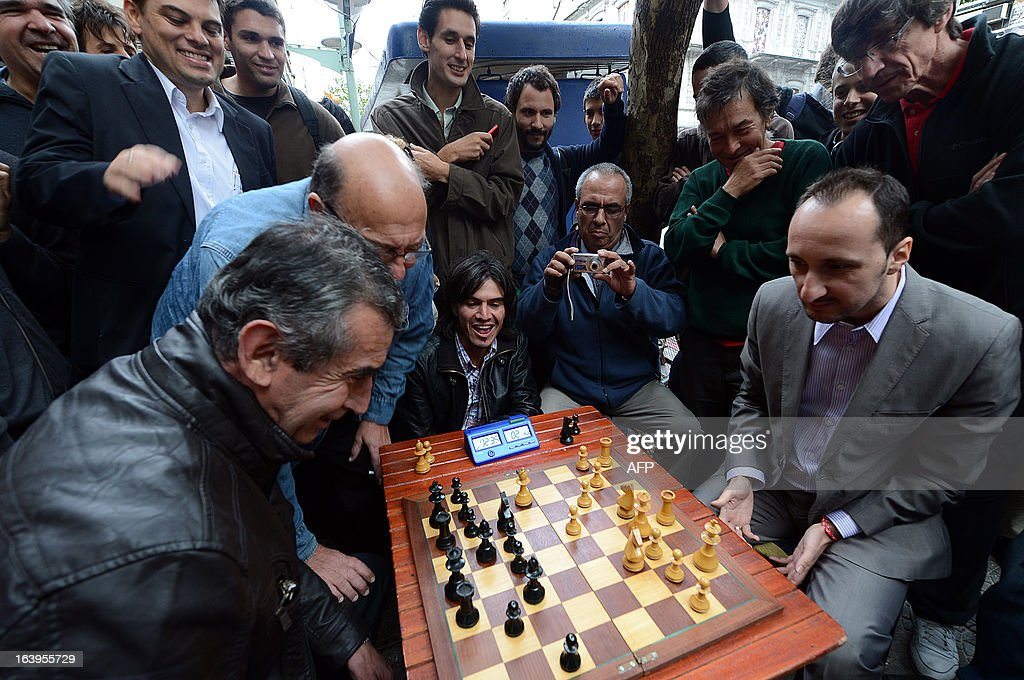 Bulgarian chess grandmaster Veselin Topalov (R) plays against Uruguayan Carlos Ferrari near to a newsstand in Montevideo on March 18, 2013. Topolov, World Chess Championship 2006, is in Uruguay to support a national program of the Minister of Education and Culture to promote chess between lower classes. Ferrari is the owner of the kiosk, next to which Montevideo citizens play chess on the sidewalk all year. AFP PHOTO / Daniel CASELLI