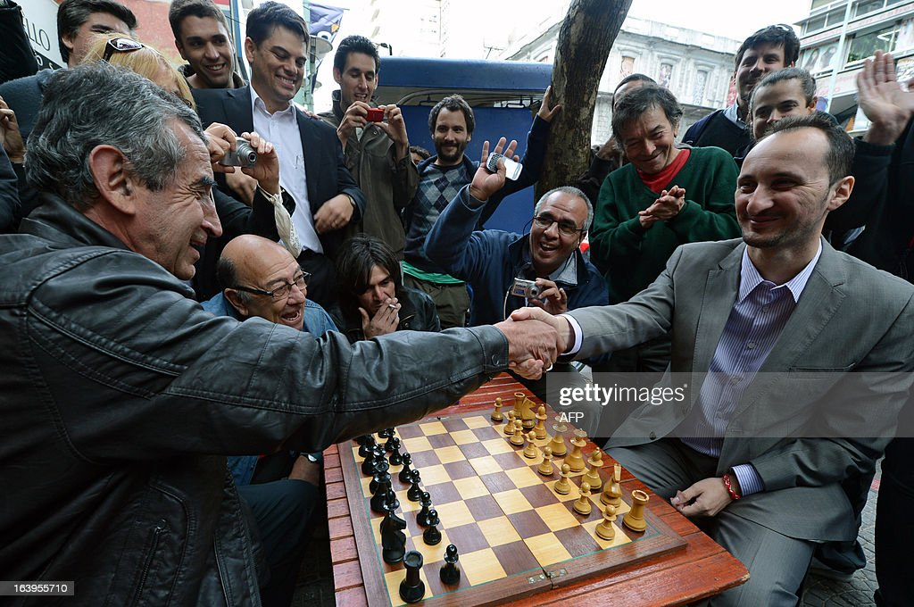 Bulgarian chess grandmaster Veselin Topalov shakes hands with Uruguayan Carlos Ferrari before playing a chess match, near to a newsstand in Montevideo on March 18, 2013. Topolov, World Chess Championship 2006, is in Uruguay to support a national program of the Minister of Education and Culture to promote chess between lower classes. Ferrari is the owner of the kiosk, next to which Montevideo citizens play chess on the sidewalk all year. AFP PHOTO / Daniel CASELLI