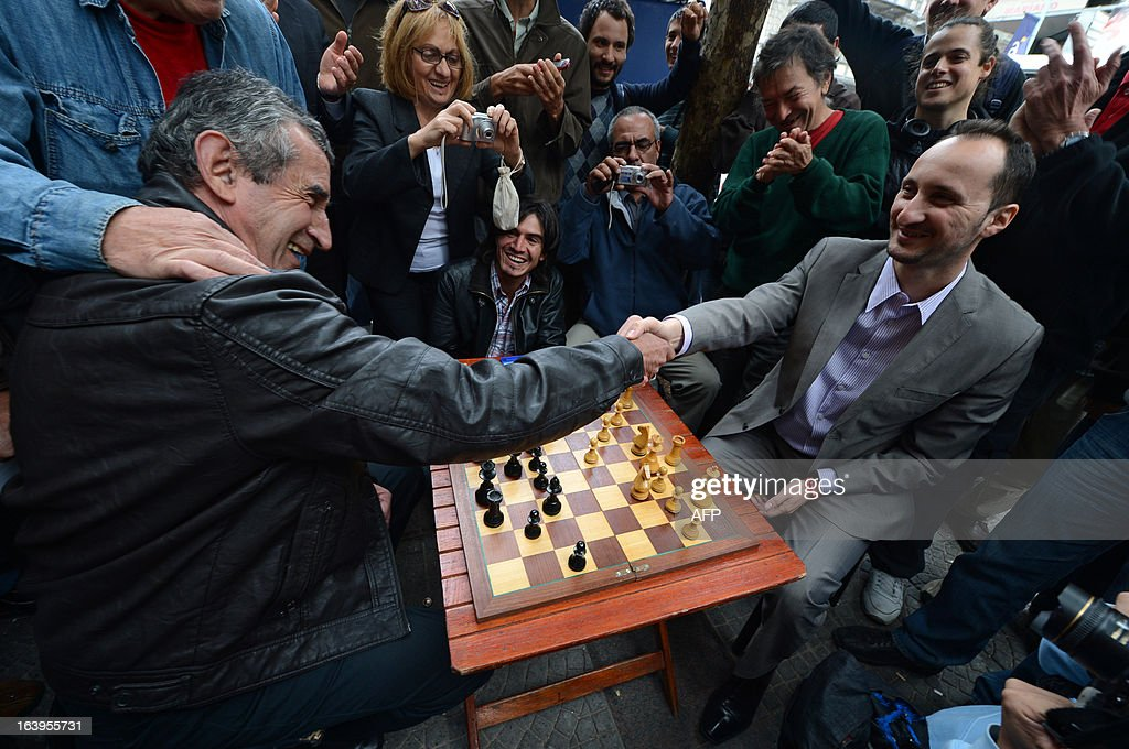 Bulgarian chess grandmaster Veselin Topalov (R) shakes hands with Uruguayan Carlos Ferrariat at the end of a match near to a newsstand in Montevideo on March 18, 2013. Topolov, World Chess Championship 2006, is in Uruguay to support a national program of the Minister of Education and Culture to promote chess between lower classes. Ferrari is the owner of the kiosk, next to which Montevideo citizens play chess on the sidewalk all year. AFP PHOTO / Daniel CASELLI