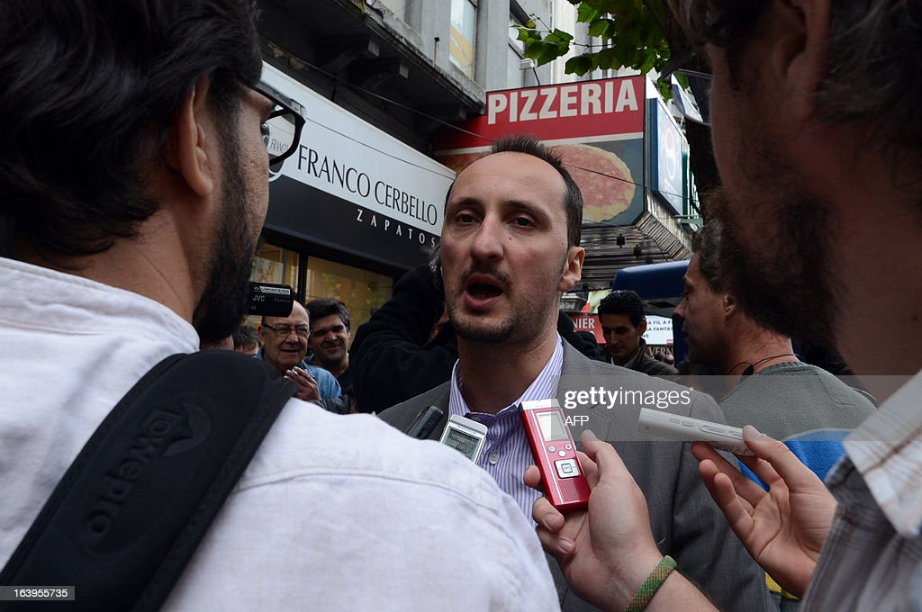 Bulgarian chess grandmaster Veselin Topalov speaks with the press at the end of a match against Uruguayan Carlos Ferrari (out of frame) near to a newsstand in Montevideo on March 18, 2013. Topolov, World Chess Championship 2006, is in Uruguay to support a national program of the Minister of Education and Culture to promote chess between lower classes. Ferrari is the owner of the kiosk, next to which Montevideo citizens play chess on the sidewalk all year. AFP PHOTO / Daniel CASELLI