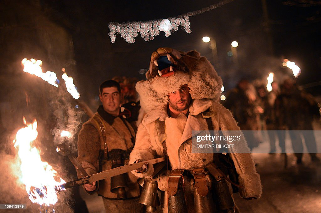 Bulgarian dancers named 'Kukeri' hold torches as they perform a ritual dance during the Kukeri Carnival in the village of Batanovci, western Bulgaria, on January 13, 2013. The Kukeri Carnival is a festival of brightly colored masks and costumes which marks the beginning of the spring. Every participant makes his own multi-colored personal mask, covered with beads, ribbons and woolen tassels. The heavy swaying of the main mummer is meant to represent wheat heavy with grain, and the bells tied around the waist are intended to drive away the evil spirits and the sickness. AFP PHOTO / DIMITAR DILKOFF