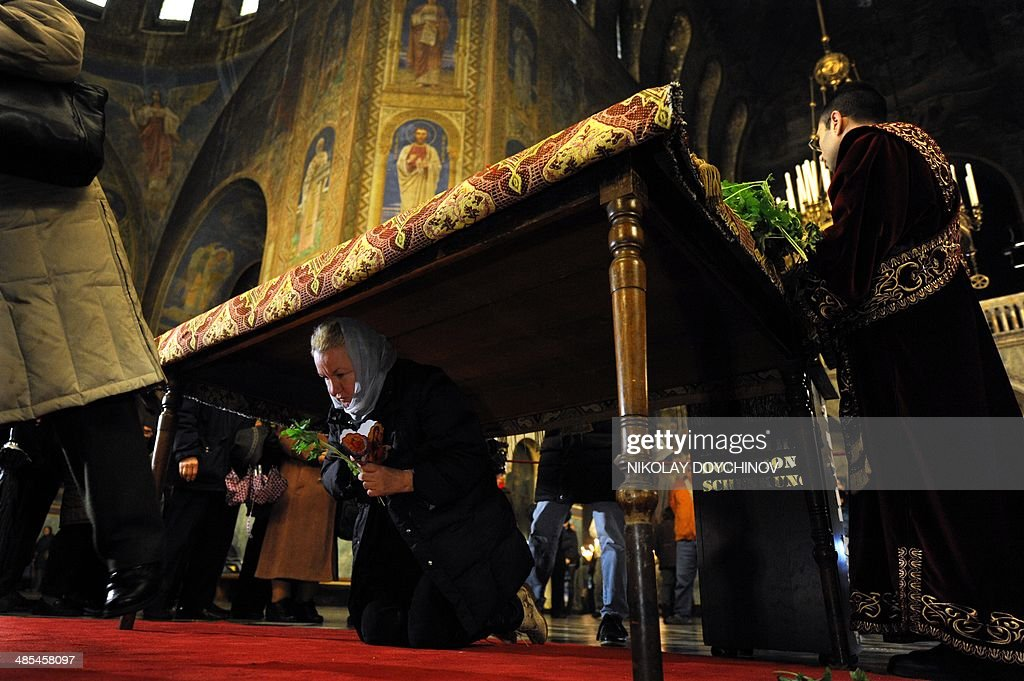 A Bulgarian Eastern-Orthodox believer passes under a table on which a Bible is placed during the Good Friday service in the golden-domed Alexander Nevsky cathedral in central Sofia on April 18, 2014.