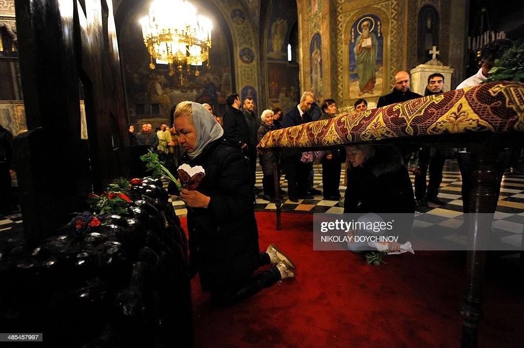 Bulgarian Eastern-Orthodox believers pray (L) and pass (R) under a table on which a Bible is placed during the Good Friday service in the golden-domed Alexander Nevsky cathedral in central Sofia on April 18, 2014. AFP PHOTO / NIKOLAY DOYCHINOV