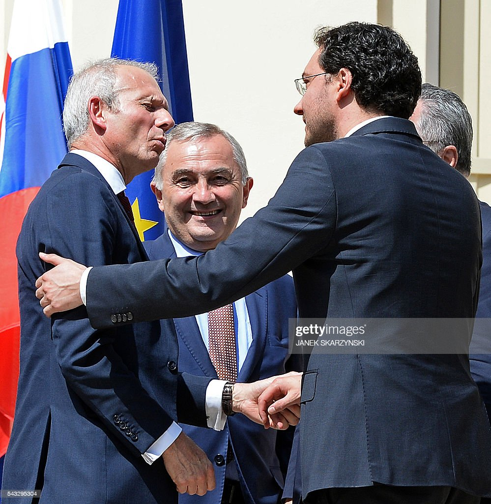 Bulgarian Foreign Minister Daniel Mitov (R) greets British Minister of State for Europe David Lidington (L) next to Foreign Minister of Romania Lazar Comanescu during a break in talks of foreign ministers and officials of several EU countries in Warsaw on June 27, 2016. / AFP / JANEK