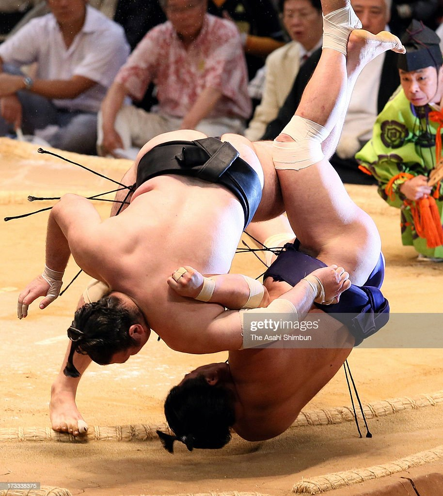 Bulgarian ozeki Kotooshu (L), whose real name is Kalojan Stefanov Mahljanov throws Myogiryu to win during day five of the Grand Sumo Nagoya Tournament at Aichi Prefecture Gymnasium on July 11, 2013 in Nagoya, Aichi, Japan.