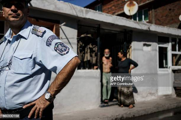 A Bulgarian policeman secures the area while teachers and social workers who are part of a team for inclusion of children and students in the...