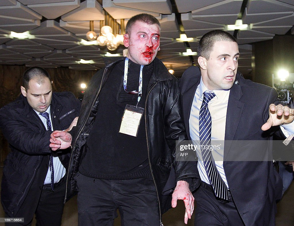 Bulgarian security officers escort a bloodied 25 year old man after he attacked Ahmed Dogan, leader of the Turkish minority Movement for Rights and Freedoms (MRF) party during his speech at a national party conference in Sofia on January 19, 2013. Dogan was addressing the delegates at the conference when the man rushed up to the podium and put a pistol to his head. The attacker however failed to produce a shot and was quickly disarmed by the delegates, witnesses told state BNR radio.
