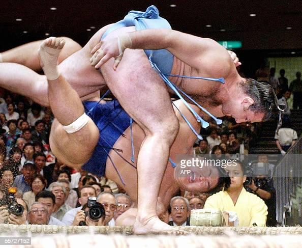 Bulgarian sekiwake ranked sumo wrestler Kotooshu throws Tomanoshima to the ground at a 10th day bout of the Autumn Grand Sumo Tournament in Toyko 20...
