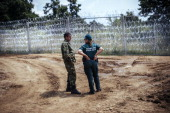 A Bulgarian soldier talks with a border police officer next to a barbed wire wall on the Bulgarian border with Turkey near the village of Golyam...