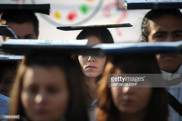 Bulgarian students carry books on their heads on November 16 2010 in front Sofia's University building in Sofia during a protest against planned...