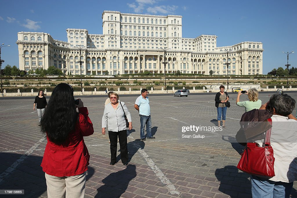 Bulgarian tourists photograph one another in front of the Palace of the Parliament, built by former Romanian dictator Nicolae Ceausescu, on September 7, 2013 in Bucharest, Romania. While the Romania's economic output has risen significantly since it joined the European Union in 2007, it still lags in infrastructure development and the fight against corruption.