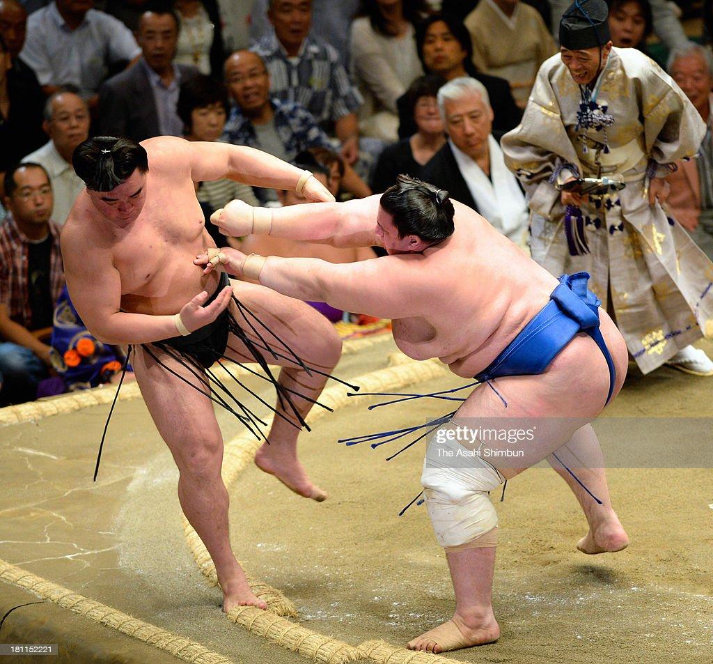 Bulgarian wrestler Aoiyama (R), whose real name is Daniel Ivanov pushes Mongolian yokozuna Harumafuji (L), whose real name is Altangadasyn Khuchitbaatar out from the ring during day four of the Grand Sumo Autumn Tournament at Ryogoku Kokugikan on September 18, 2013 in Tokyo, Japan.