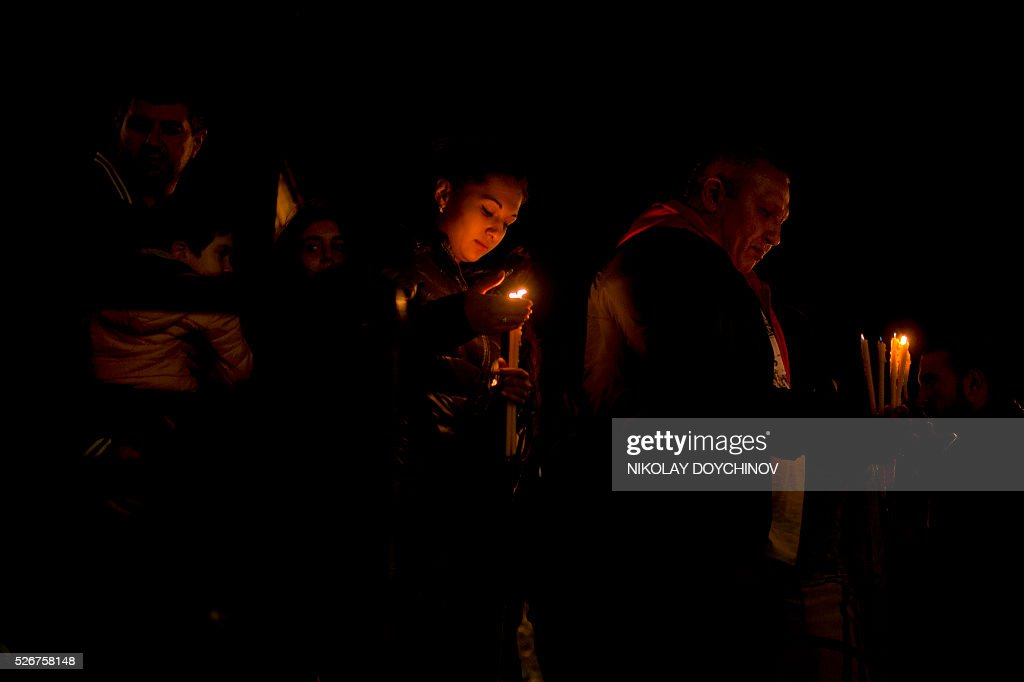 Bulgarians walk with candles near the golden-domed Alexander Nevski Cathedral after an Easter service in Sofia early on May 1, 2016. Orthodox Christians are celebrating Easter Sunday on May 1. / AFP / NIKOLAY