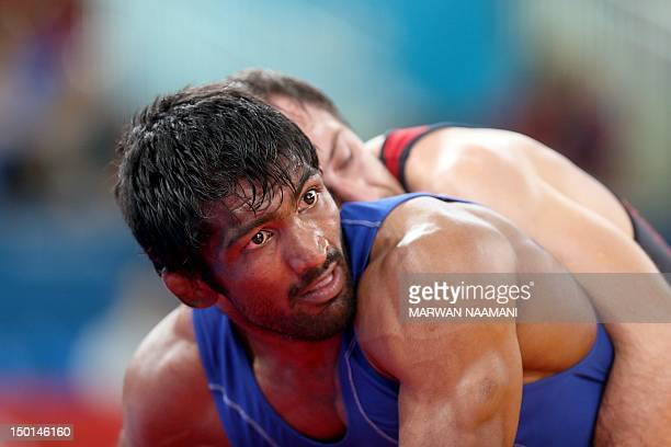 Bulgaria's Anatolie Ilarionovitch Guidea wrestles India's Yogeshwar Dutt in their Men's 60kg Freestyle qualification match on August 11 2012 during...