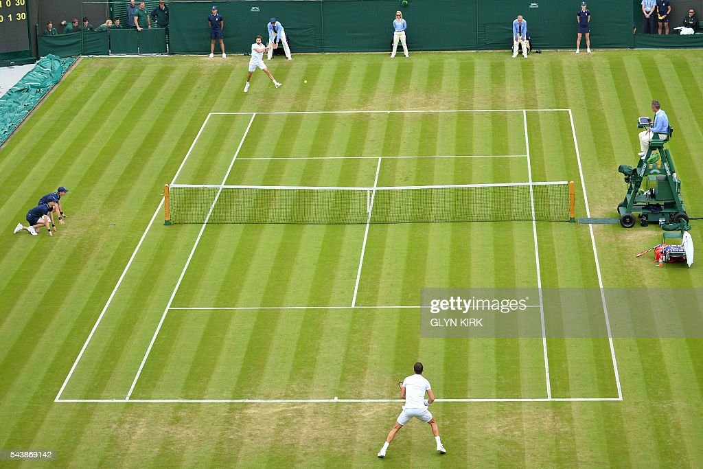 Bulgaria's Grigor Dimitrov (bottom) and France's Gilles Simon (top) play during their men's singles second round match on the fourth day of the 2016 Wimbledon Championships at The All England Lawn Tennis Club in Wimbledon, southwest London, on June 30, 2016. / AFP / GLYN