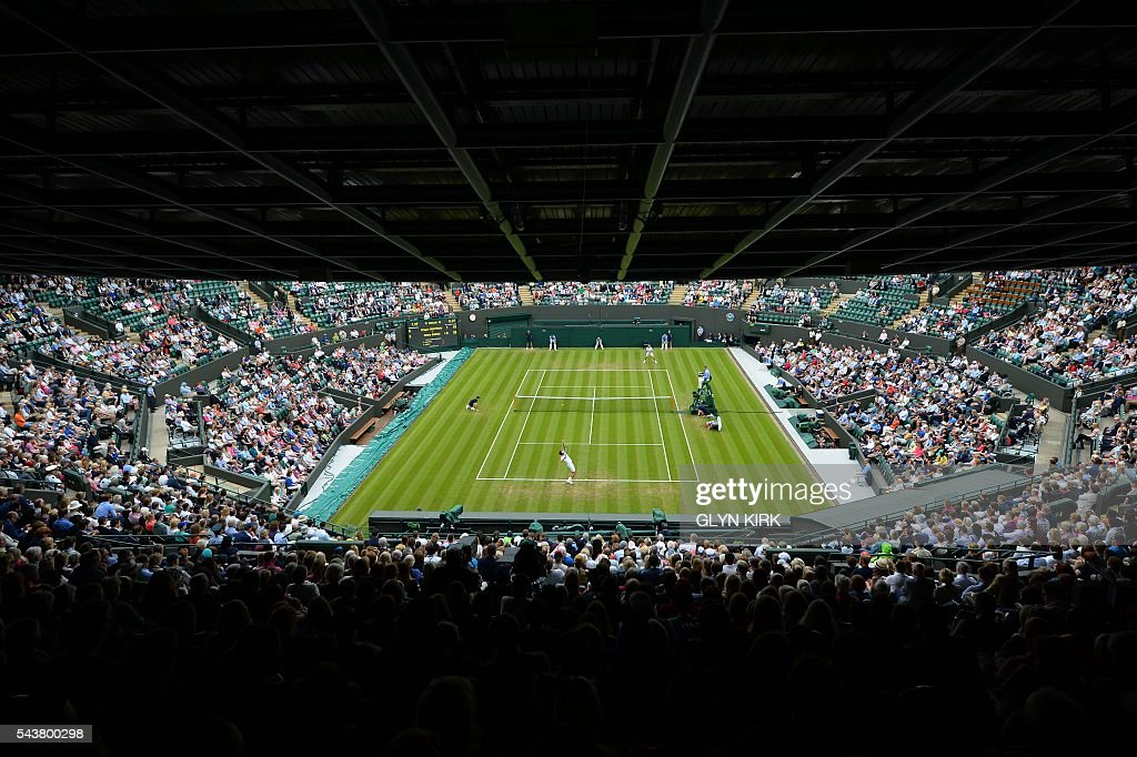Bulgaria's Grigor Dimitrov serves against France's Gilles Simon during their men's singles second round match on the fourth day of the 2016 Wimbledon Championships at The All England Lawn Tennis Club in Wimbledon, southwest London, on June 30, 2016. / AFP / GLYN